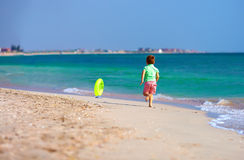 Gelukkige jongen die het strand voor rubberring in werking stellen Royalty-vrije Stock Afbeeldingen