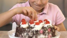 Gelukkige jongen die kers vanaf bovenkant van roomcake eten, ongezond dieet, gastro-enterologie stock videobeelden