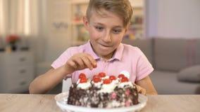 Gelukkige jongen die kers vanaf bovenkant van roomcake eten, zoet dessert, kinderjarensnack stock video