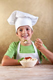 Gelukkige jongen die met chef-kokhoed deegwaren eet Stock Foto's