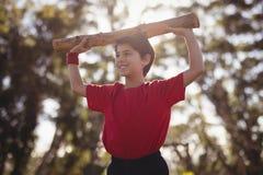 Gelukkige jongen die met logboek tijdens hinderniscursus uitoefenen royalty-vrije stock fotografie