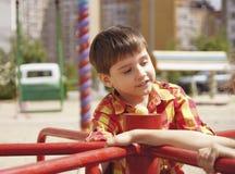 Gelukkige jongen die op een spinnende schommeling berijden royalty-vrije stock foto