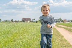 Gelukkige jongen die op het gebied lopen Stock Afbeelding