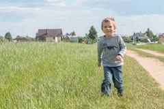 Gelukkige jongen die op het gebied lopen Stock Fotografie
