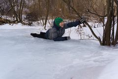 Gelukkige jongen die op het ijs in de middag in de winter liggen stock afbeelding