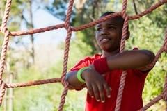 Gelukkige jongen die op netto tijdens hinderniscursus leunen stock afbeelding