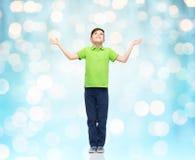 Gelukkige jongen die in polot-shirt handen omhoog opheffen Stock Afbeeldingen