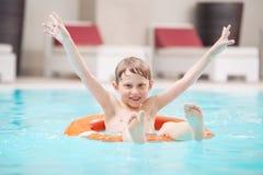 Gelukkige jongen die in pool zwemmen Stock Foto's