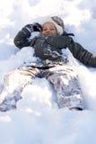 Gelukkige Jongen die in Verse Sneeuw legt stock fotografie