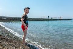 Gelukkige jongen die zich voor het overzees op een strand bevinden royalty-vrije stock afbeelding