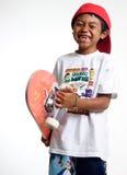 Gelukkige jongen die zijn skateboard houdt stock afbeelding