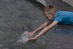 Gelukkige jongen door de fontein in de stad in heet weer stock afbeelding