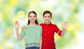 Gelukkige jongen en meisjes golvende hand Stock Afbeelding