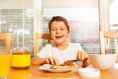 Gelukkige jongen het uitspreiden chocolade met mes op toost stock afbeeldingen