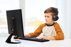 Gelukkige jongen met computer en hoofdtelefoons thuis Stock Afbeelding