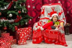 Gelukkige jongen met de zitting van de Kerstmanhoed als voorzitter stock fotografie