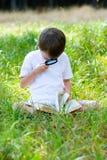 Gelukkige jongen met een vergrootglas en een boek stock foto