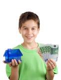 Gelukkige jongen met geld en huis in zijn hand stock foto's