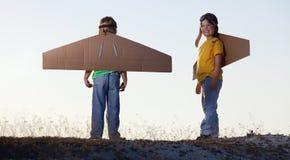 Gelukkige jongen met kartondozen van vleugels tegen hemeldroom van vlieg royalty-vrije stock afbeeldingen