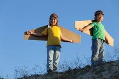 Gelukkige jongen met kartondozen van vleugels tegen hemeldroom van vlieg royalty-vrije stock foto