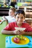 Gelukkige jongen met klasgenoten die maaltijd hebben royalty-vrije stock afbeeldingen