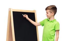 Gelukkige jongen met krijt en leeg schoolbord Stock Foto's