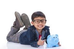 Gelukkige jongen met spaarvarken Stock Fotografie