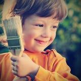 Gelukkige jongen met verfborstel stock afbeeldingen