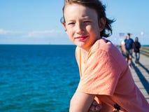 Gelukkige jongen op een pijler bij Oostzee stock fotografie