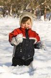 Gelukkige jongen op sneeuw Stock Foto's