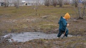 Gelukkige jongen in waterdichte overalllooppas door een vulklei in de lente stock video