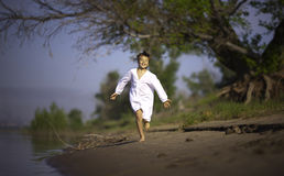 Gelukkige jongen in wit overhemd, die langs de rivierbank lopen Royalty-vrije Stock Afbeeldingen