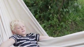 Gelukkige jongens blonde slaap in hangmat in de zomer bij het plattelandshuisje stock footage
