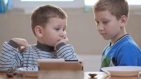 Gelukkige jongens die een diner gaan hebben Kijkend voordien een tablet stock footage