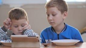 Gelukkige jongens die op diner wachten Kijkend voordien een tablet stock videobeelden