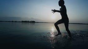 Gelukkige jongenslooppas langs het strand bij zonsondergang Langzame Motie stock video