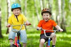 Gelukkige jongensvrienden op fiets in groen park Royalty-vrije Stock Foto
