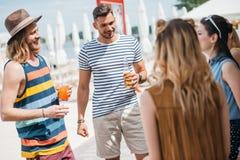 gelukkige jongeren die dranken drinken en elkaar bekijken stock afbeeldingen