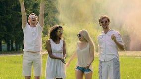Gelukkige jongeren die samen gekleurd poeder in lucht werpen, die pret hebben bij partij stock video