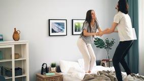 Gelukkige jongeren in pyjama's die samen op bed dansen die thuis pret hebben stock footage