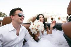 Gelukkige jonggehuwden in de auto Stock Afbeelding