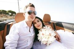 Gelukkige jonggehuwden in de auto Stock Foto's