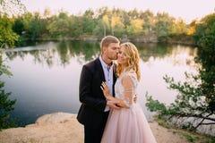 Gelukkige jonggehuwden die zich tegen aardachtergrond bij zonsondergang bevinden Stock Foto