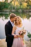 Gelukkige jonggehuwden die zich tegen aardachtergrond bij zonsondergang bevinden Stock Afbeeldingen