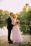 Gelukkige jonggehuwden die zich tegen aardachtergrond bij zonsondergang bevinden Royalty-vrije Stock Afbeelding