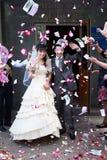 Gelukkige jonggehuwden en vliegende bloemblaadjes Royalty-vrije Stock Foto's
