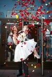 Gelukkige jonggehuwdenbruid en bruidegom met bloemblaadjes Stock Foto