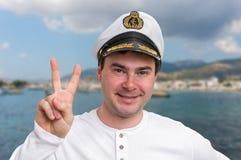 Gelukkige kapitein met zeeman GLB die overwinningsteken tonen royalty-vrije stock afbeeldingen