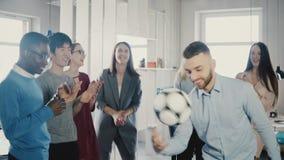 Gelukkige Kaukasische arbeider het jongleren met voetbal op hoofd De vrolijke gemengde rasstafmedewerkers vieren bedrijfssucces i stock video