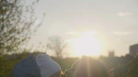 Gelukkige Kaukasische moeder en peuterdochter in openlucht in park op zonnige de lentedag Jonge donkerbruine moeder die haar ophe stock video